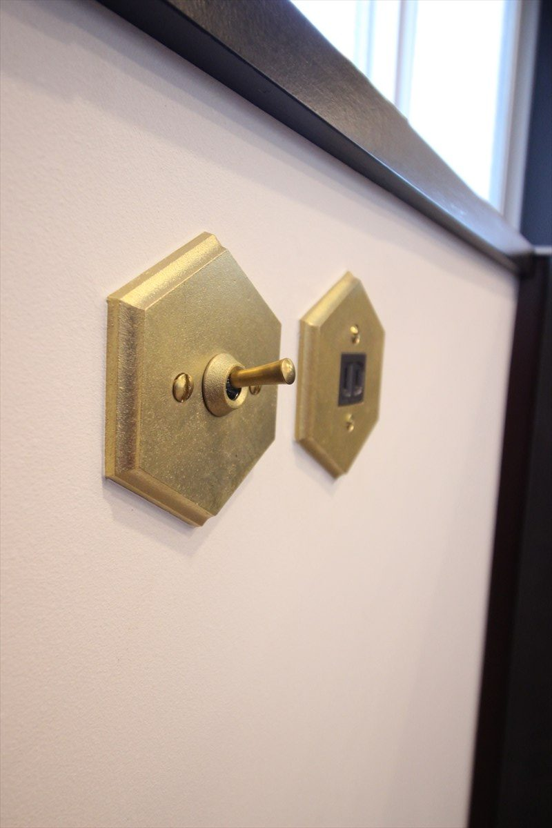 キッチン横に付けたマットゴールドのスイッチとコンセント 横浜リノベーション