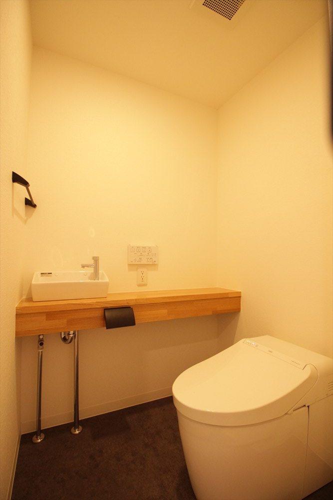 ダークトーンの床と木材アクセントのトイレ|リノベーション横浜